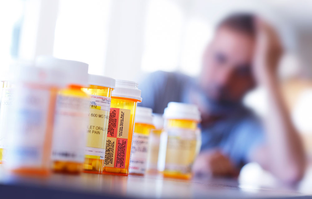 Prescription drugs in the foreground and a man in the background staring at them