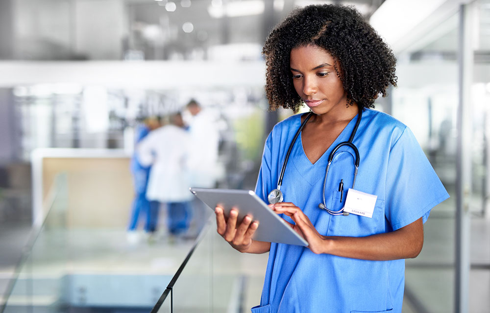young medical professional woman looking up something on a tablet
