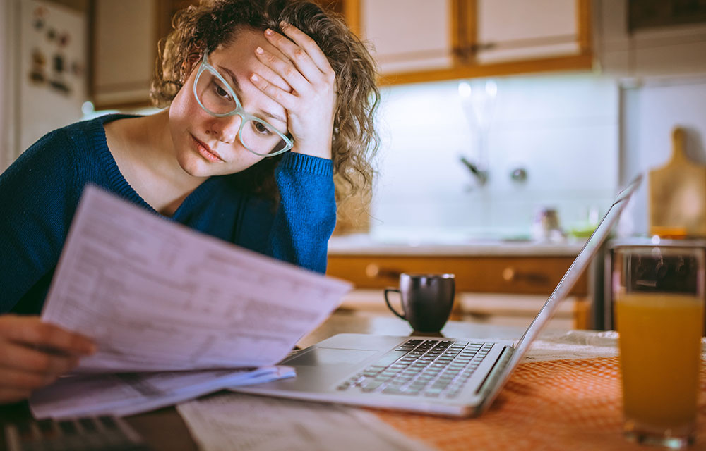Woman in kitchen reviewing finances